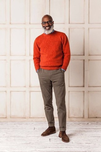 How to wear: brown suede desert boots, brown chinos, light blue denim shirt, orange crew-neck sweater