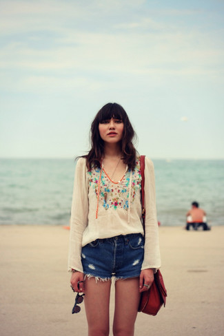 How to wear: burgundy leather crossbody bag, blue ripped denim shorts, white embroidered peasant blouse