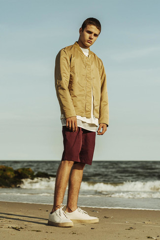 How to wear: white canvas low top sneakers, burgundy shorts, white and black horizontal striped crew-neck t-shirt, tan bomber jacket