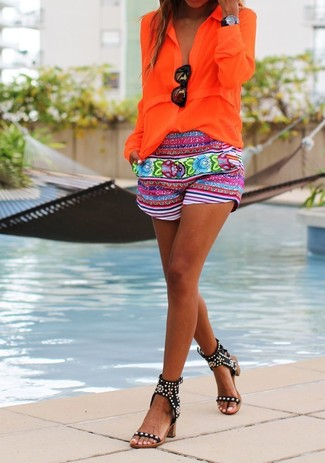 How to wear: orange button down blouse, multi colored floral shorts, black studded leather heeled sandals, black sunglasses