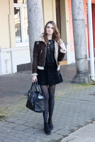 How to wear: black suede chelsea boots, black button skirt, black embroidered crew-neck t-shirt, dark brown shearling jacket