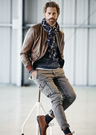 How to wear: brown suede desert boots, grey cargo pants, navy crew-neck sweater, brown leather bomber jacket
