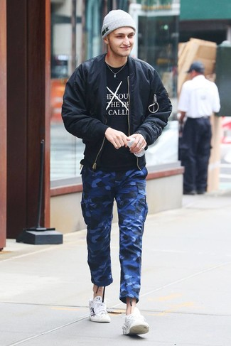 How to wear: white print leather low top sneakers, blue camouflage cargo pants, black and white print crew-neck t-shirt, black bomber jacket