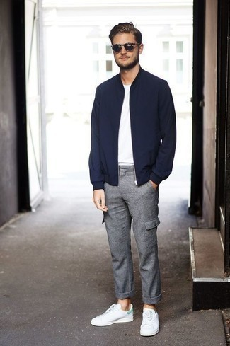 Men's Looks & Outfits: What To Wear In 2020: A navy bomber jacket and grey wool cargo pants are a good combo to have in your day-to-day styling routine. As for footwear, complete this look with a pair of white and green leather low top sneakers.