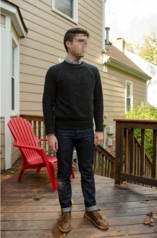Look sharp without really trying in a dark grey crew-neck sweater and navy blue jeans. A pair of brown leather desert boots looks proper here. Rest assured, this getup will keep you toasty as well as looking stylish in this in-between weather.