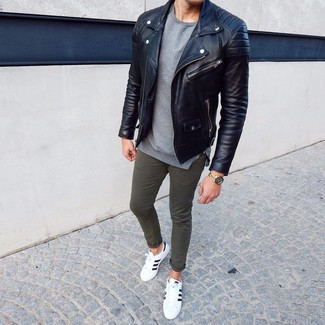 How to wear: white and black leather low top sneakers, olive chinos, grey crew-neck sweater, black leather biker jacket