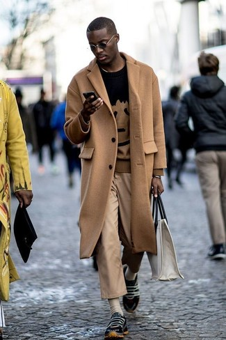 How to wear: black athletic shoes, khaki chinos, black print crew-neck sweater, camel overcoat