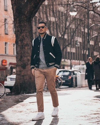 How to wear: white low top sneakers, khaki chinos, grey crew-neck sweater, black and white varsity jacket