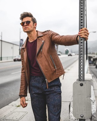 How to wear: dark brown sunglasses, navy floral chinos, burgundy crew-neck t-shirt, brown leather biker jacket