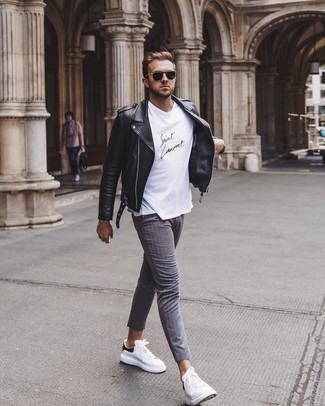 How to wear: white and black leather low top sneakers, grey vertical striped chinos, white and black crew-neck t-shirt, black leather biker jacket