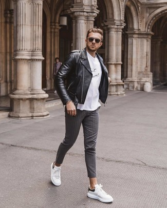 How to wear: white and black leather low top sneakers, grey vertical striped chinos, white and black print crew-neck t-shirt, black leather biker jacket