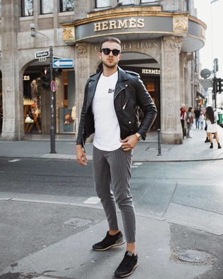 How to wear: black low top sneakers, grey vertical striped chinos, white and black print crew-neck t-shirt, black leather biker jacket