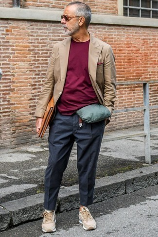 Fashion for Men Over 60: What To Wear: A brown double breasted blazer and charcoal chinos are among the fundamental elements in any gentleman's classic and casual wardrobe. A trendy pair of tan suede low top sneakers is an easy way to transform your outfit.
