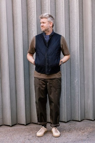 How to Wear a Navy Gilet For Men: Try teaming a navy gilet with dark brown chinos to feel confident and look stylish. Inject a mellow touch into your ensemble by finishing with a pair of beige canvas low top sneakers.