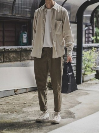 Men's Looks & Outfits: What To Wear In 2020: A beige long sleeve shirt and olive chinos will give off this casually dapper vibe. Complement your look with a pair of white canvas high top sneakers to infuse a sense of stylish casualness into your outfit.