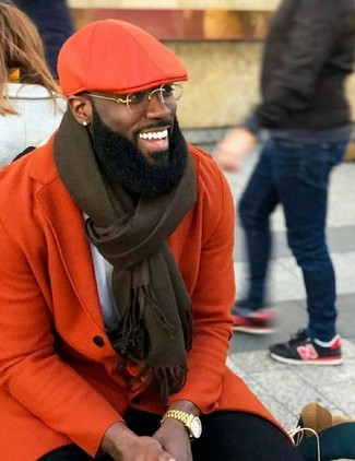 How to wear: orange flat cap, black chinos, white crew-neck t-shirt, orange overcoat
