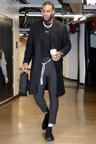 How to wear: black athletic shoes, black and white vertical striped chinos, black and white print crew-neck t-shirt, black overcoat