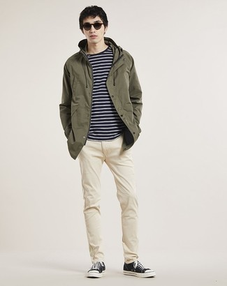 How to Wear Beige Chinos: In fashion situations comfort is prized, make an olive parka and beige chinos your outfit choice. Complement your ensemble with black and white canvas low top sneakers and the whole ensemble will come together.