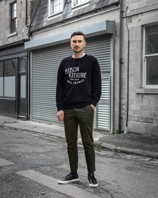 How to Wear Olive Chinos: Sharp yet comfortable, this look is assembled from a black and white print sweatshirt and olive chinos. A pair of black leather low top sneakers acts as the glue that pulls this outfit together.