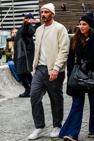 Men's Looks & Outfits: What To Wear In 2020: You'll be surprised at how easy it is for any man to get dressed this way. Just a beige varsity jacket and navy vertical striped chinos. Complement your outfit with white leather low top sneakers and off you go looking incredible.