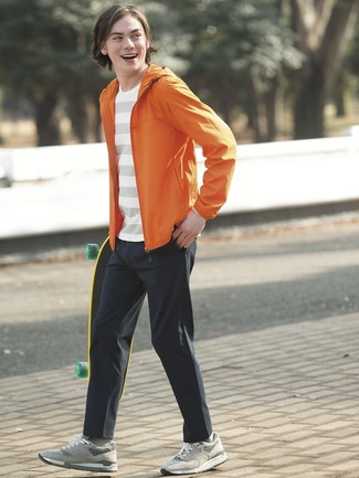 How to wear: grey suede low top sneakers, black chinos, white horizontal striped crew-neck t-shirt, orange windbreaker