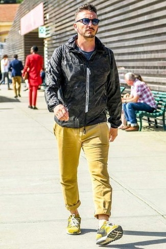 How to wear: yellow athletic shoes, yellow chinos, navy crew-neck t-shirt, black windbreaker