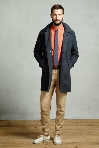 How to wear: beige canvas low top sneakers, khaki chinos, orange dress shirt, black trenchcoat