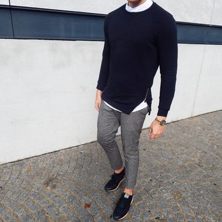 How to wear: black leather low top sneakers, grey chinos, white long sleeve shirt, navy crew-neck sweater