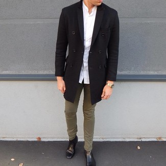 How to wear: black leather chelsea boots, olive chinos, white long sleeve shirt, black overcoat