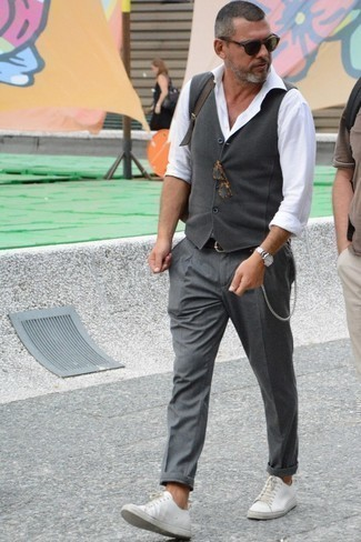 How to Wear a Grey Waistcoat: This combination of a grey waistcoat and grey chinos is the picture of sophistication. Infuse a more laid-back vibe into this look with white leather low top sneakers.