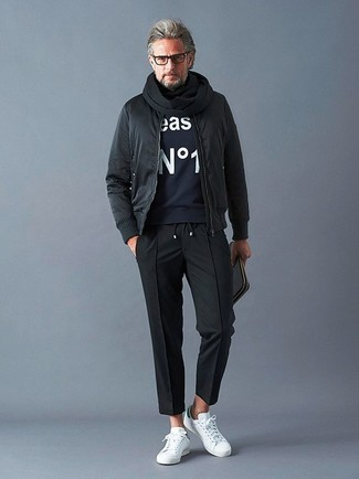 How to wear: white leather low top sneakers, black chinos, navy print sweatshirt, black bomber jacket