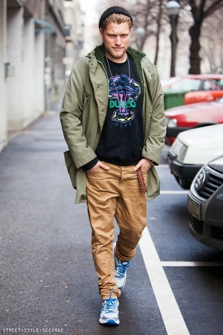 How to wear: white athletic shoes, khaki chinos, black print sweatshirt, olive parka