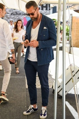 How to Wear a White Tank For Men: A white tank and navy chinos are great menswear staples that will integrate nicely within your off-duty fashion mix. A pair of navy and white canvas low top sneakers is a good pick to finish your ensemble.