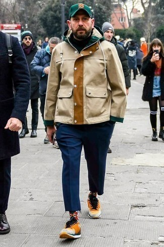 Men's Looks & Outfits: What To Wear In Cold Weather: This laid-back pairing of a tan parka and navy chinos is a foolproof option when you need to look cool but have no extra time. Complement your outfit with a pair of orange athletic shoes to add a touch of stylish nonchalance to your outfit.