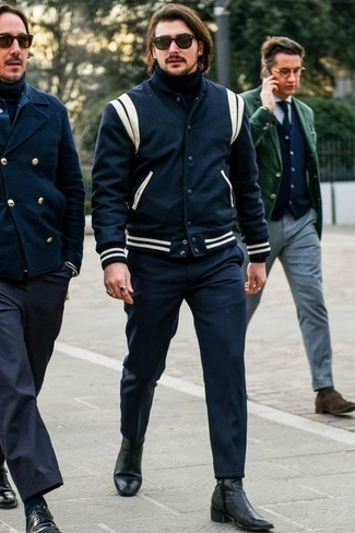 Men's Looks & Outfits: What To Wear In 2020: This casual combination of a navy and white varsity jacket and navy chinos can only be described as incredibly stylish. And if you wish to instantly dial up your look with footwear, why not complete this outfit with black leather chelsea boots?