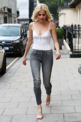 How to Wear Clear Rubber Heeled Sandals: This combination of a white bustier top and grey ripped skinny jeans is definitive proof that a safe casual ensemble can still be really interesting. And if you need to immediately rev up this ensemble with one piece, add clear rubber heeled sandals to this outfit.