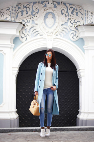 A nicely put together combination of a light blue coat and blue ripped skinny jeans will set you apart effortlessly. White low top sneakers will add some edge to an otherwise classic look.