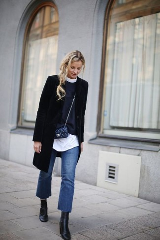 How to wear: black coat, white tunic, black crew-neck sweater, blue flare jeans