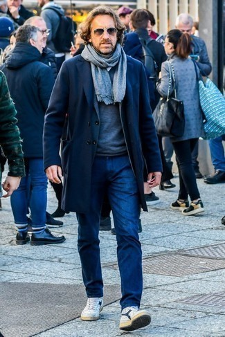Men's Looks & Outfits: What To Wear In Winter: Marry a navy overcoat with navy jeans and you'll look truly stylish anywhere anytime. Don't know how to round off? Complement this outfit with a pair of white and navy leather high top sneakers to shake things up. While dressing for wintertime can be a bit of a challenge, it's getups like this that make you feel excited.