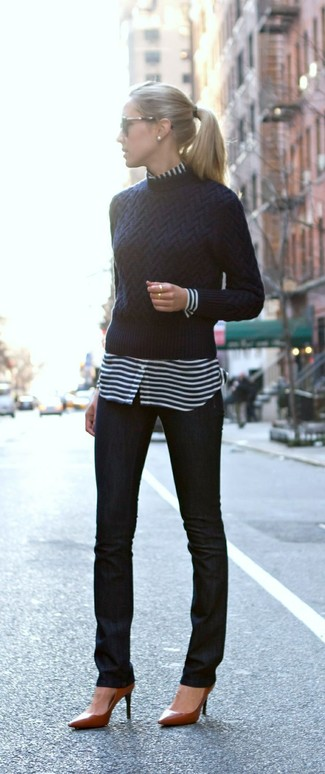 Let everyone know that you know a thing or two about style in a dark blue crew-neck pullover and black skinny jeans. Brown leather pumps will bring a classic aesthetic to the ensemble.