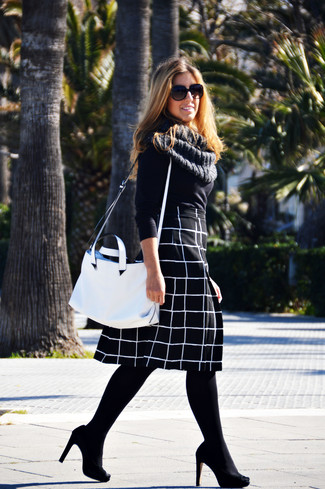 If you don't like getting too predictable with your combinations, consider pairing a black crew-neck pullover with a black and white check full skirt. Why not introduce black suede pumps to the mix for an added touch of style? We promise this combo is the answer to all of your spring dressing woes.