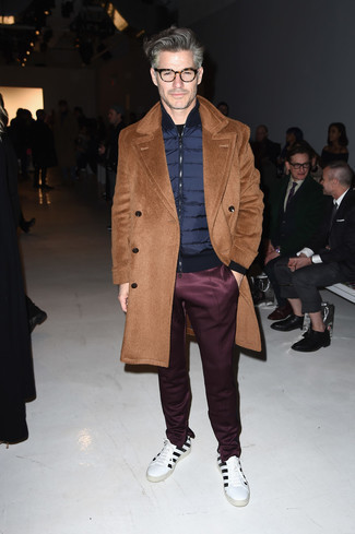 Men's Looks & Outfits: What To Wear In Chill Weather: Who said you can't make a stylish statement with a relaxed ensemble? Turn every head in the room in a camel overcoat and burgundy sweatpants. For an on-trend on and off-duty mix, introduce white and black horizontal striped leather low top sneakers to the mix.