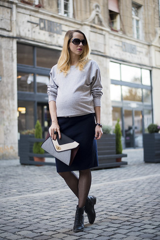 How to wear: grey crew-neck sweater, navy pencil skirt, black leather lace-up flat boots, grey leather clutch