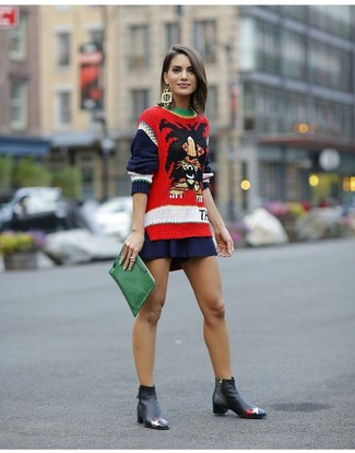 How to wear: red print crew-neck sweater, navy skater skirt, black leather chelsea boots, green leather clutch
