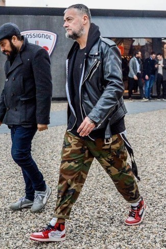 How to Wear a Black Leather Biker Jacket For Men: You're looking at the irrefutable proof that a black leather biker jacket and brown camouflage cargo pants are amazing when matched together in an off-duty outfit. Introduce a pair of white and red leather high top sneakers to the equation and off you go looking awesome.