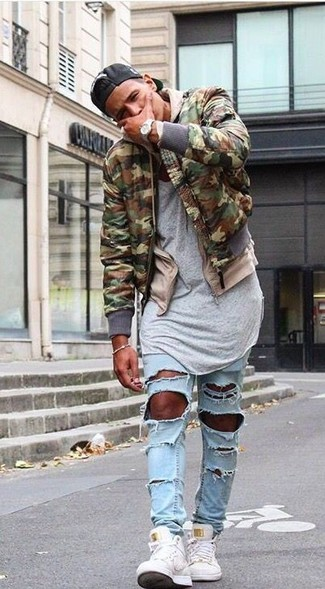 How to Wear an Olive Camouflage Bomber Jacket For Men: Marry an olive camouflage bomber jacket with light blue ripped skinny jeans for relaxed dressing with a twist. When in doubt as to the footwear, finish with a pair of white canvas high top sneakers.
