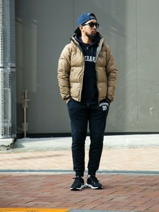 How to wear: black sweatpants, black crew-neck t-shirt, black and white print hoodie, tan puffer jacket