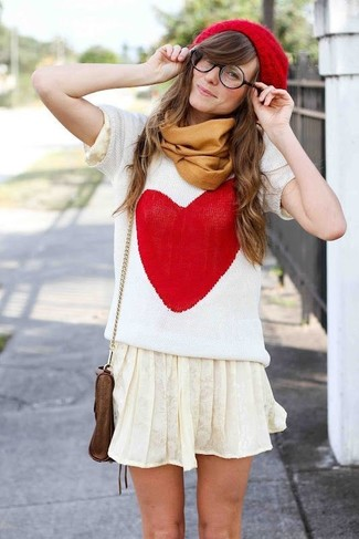 How to wear: red beanie, brown leather crossbody bag, beige pleated mini skirt, white and red print short sleeve sweater