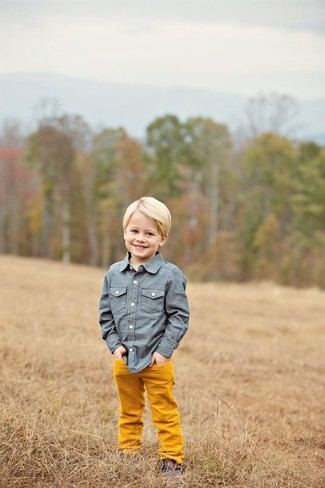 How to Wear Yellow Trousers For Boys: Dress your little angel in a blue chambray long sleeve shirt and yellow trousers to help him look like a true little gent. This getup is complemented really well with dark brown desert boots.