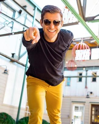 How to wear: dark brown sunglasses, mustard chinos, black long sleeve shirt